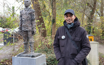 Sergio Berrenstein stands next to the statue of Elieser at the entrance to the Jewish cemetery in Ouderkerk aan de Amstel, the Netherlands, November 20, 2020. (Cnaan Liphshiz/ JTA)