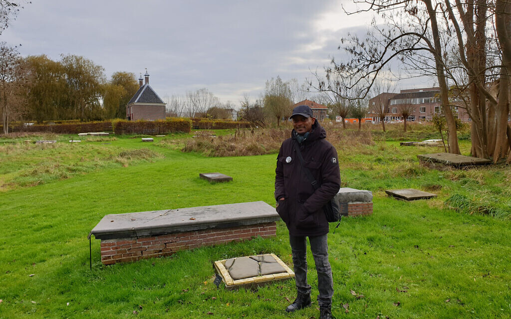 Sergio Berrenstein stands next to the grave of Elieser and his master at the entrance to the Jewish cemetery in Ouderkerk aan de Amstel, the Netherlands, November 20, 2020. (Cnaan Liphshiz/ JTA)