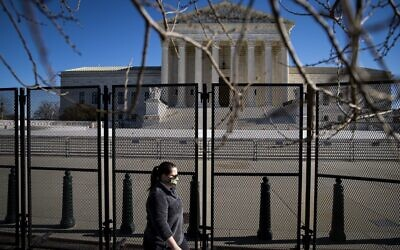 A woman walks past protective fencing erected around the US Supreme Court, on January 10, 2021 in Washington, DC.   Al Drago/Getty Images/AFP