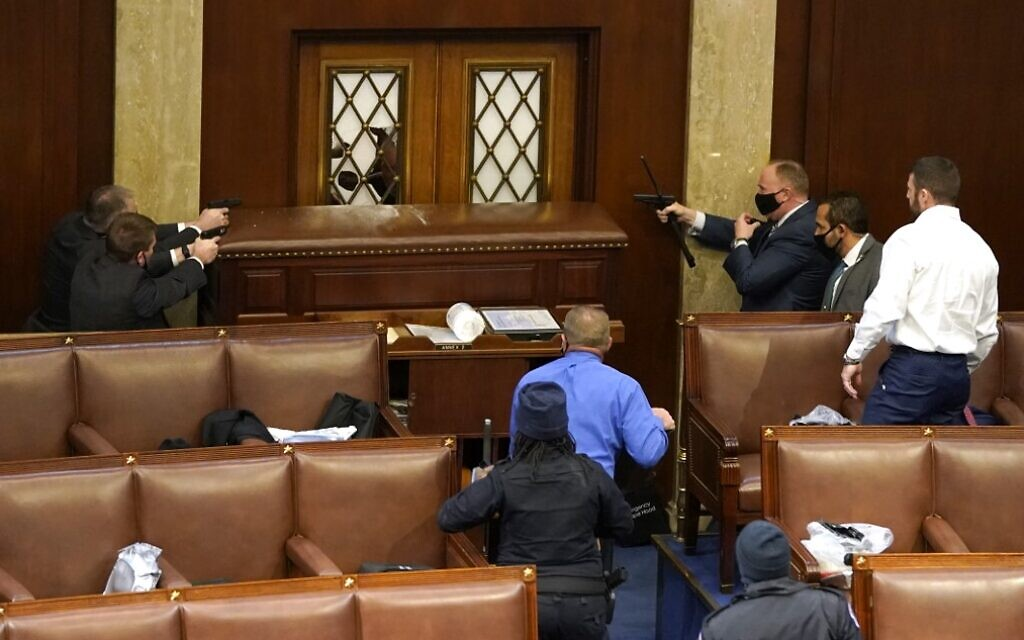US Capitol police officers point their guns at a door that was vandalized in the House Chamber during a joint session of Congress on January 6, 2021, in Washington. (Drew Angerer/Getty Images/AFP)