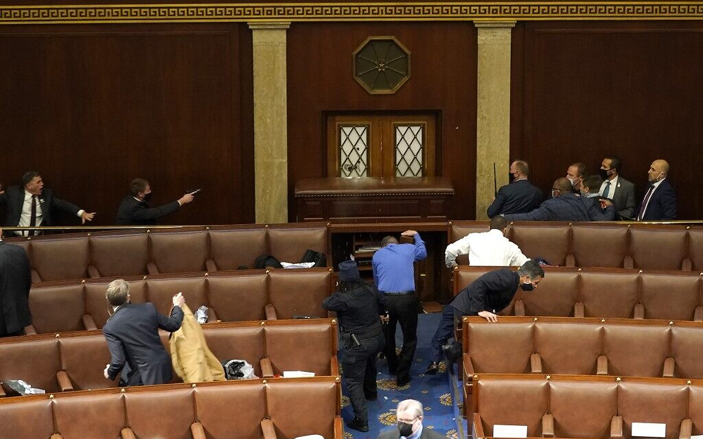 US Capitol police officers point their guns at a door that was vandalized in the House Chamber during a joint session of Congress on January 6, 2021 in Washington, DC. (Drew Angerer/Getty Images/AFP)