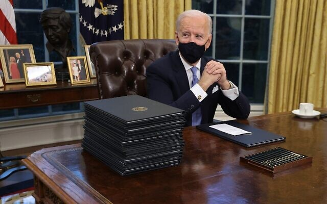 US President Joe Biden prepares to sign a series of executive orders at the Resolute Desk in the Oval Office just hours after his inauguration on January 20, 2021 in Washington, DC. (Chip Somodevilla/Getty Images/AFP)
