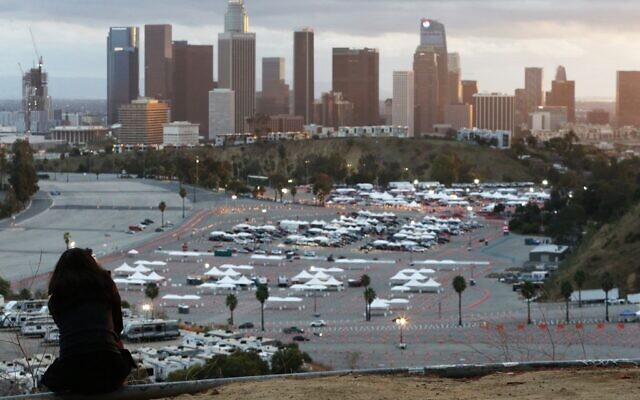 A person sits on a hillside as cars are lined up with people waiting to receive vaccines at a mass COVID-19 vaccination site at Dodger Stadium, with the downtown skyline in the background, on January 22, 2021 in Los Angeles, California. (Mario Tama/Getty Images/AFP)