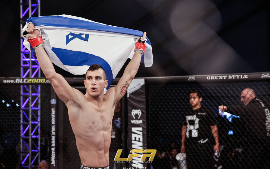 Natan Levy proudly shows an Israeli flag before his matches. (Amy Kaplan/ via JTA)