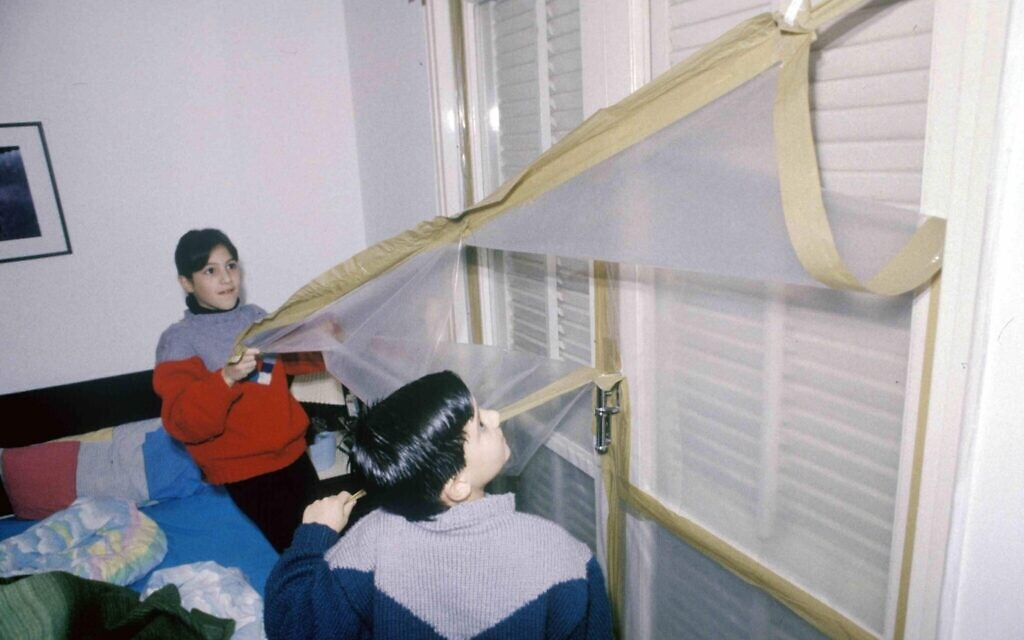 Israeli children pull down protective plastic sheeting from windows that was meant to protect them from chemical weapons in a Scud missile attack during the 1991 First Gulf War. (Michael Tzarfati/Defense Ministry Archive)
