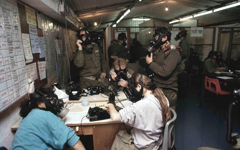 Military officials in a command center wear gas masks during a Scud missile attack on Israel during the 1991 First Gulf War. (Noam Wind, Asaf Topaz and Michael Tzarfati/Defense Ministry Archive)