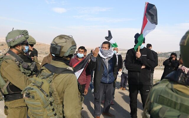 Palestinians protest Israeli policies and settler attacks in the south Hebron Hills as soldiers look on, January 2, 2021. (WAFA)