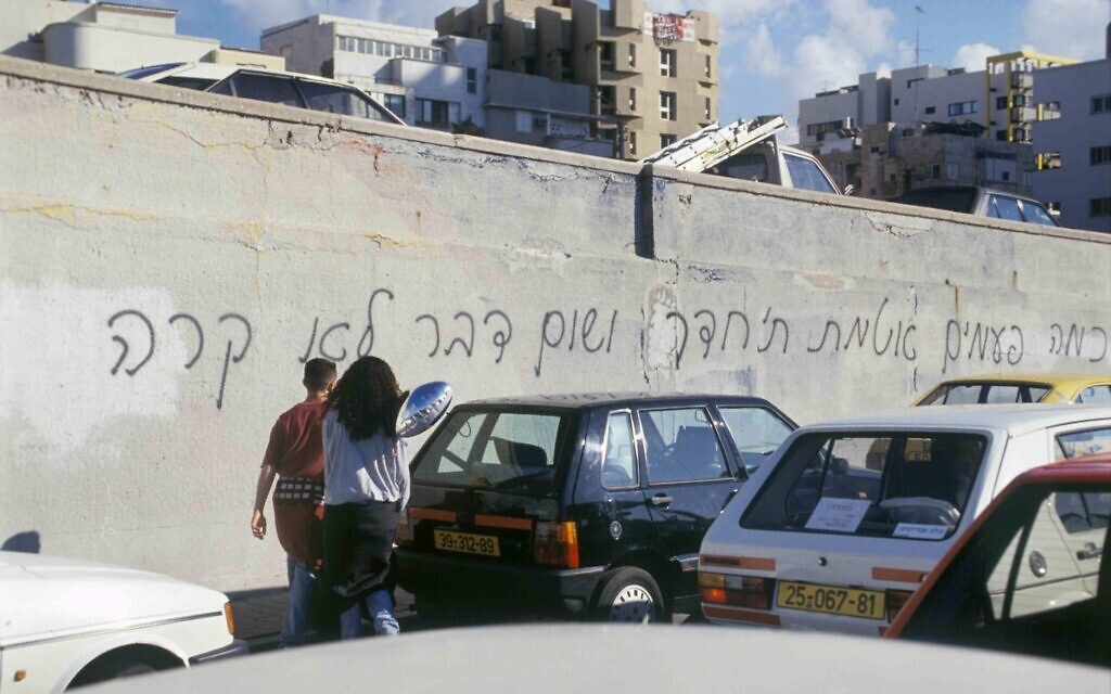 Israelis walk by graffiti reading, 'How many times did you seal the room and nothing happened,' referencing Rafi Persky song, in regard to the Scud missile attacks on Israel during the 1991 First Gulf War, which Israeli feared would carry chemical or biological weapons. (Alex Lebac/Defense Ministry Archive)