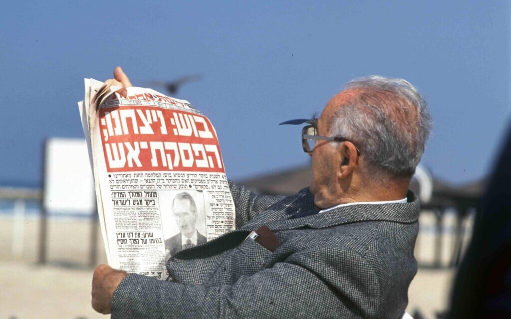 A man on the beach reads a newspaper with the headline, 'Bush: We won; a ceasefire,' referring to the end of the 1991 First Gulf War. (Defense Ministry Archive)