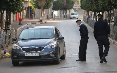 Palestinian police check cars in Ramallah as part of enforcing a coronavirus lockdown on January 1, 2021 (WAFA)