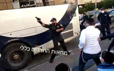 A police officer shoots in the air during a clash with ultra-Orthodox rioters protesting the enforcement of a lockdown ordered due to the coronavirus, in the city of Bnei Brak, January 24, 2021. (Screen capture: Twitter)