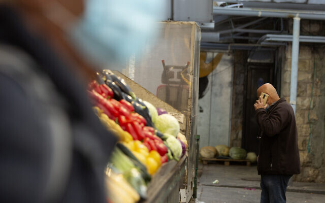 A man in a protective mask passes another man talking on his mobile phone at the Mahane Yehuda market in Jerusalem, December 23, 2020. (Maya Alleruzzo/AP)
