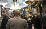 A man speaks on his mobile phone at the Mahane Yehuda market in Jerusalem, December 23, 2020. (Maya Alleruzzo/AP)