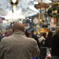 A man speaks on his mobile phone at the Mahane Yehuda market in Jerusalem, December 23, 2020. (Maya Alleruzzo/AP)