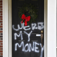 Graffiti reading, 'Where's my money' is seen on a door of the home of Senate Majority Leader Mitch McConnell in Louisville, Kentucky, Jan. 2, 2021    (AP Photo/Timothy D. Easley)