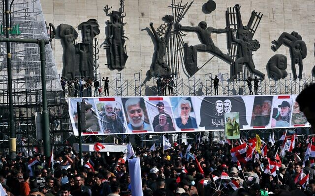 Supporters of the Popular Mobilization Forces hold a posters of Abu Mahdi al-Muhandis, deputy commander of the Popular Mobilization Forces, front, and General Qassem Soleimani, head of Iran's Quds force during a protest marking a year since their killing in a US drone strike, in Tahrir Square, Iraq, January 3, 2021. (Khalid Moha/AP)