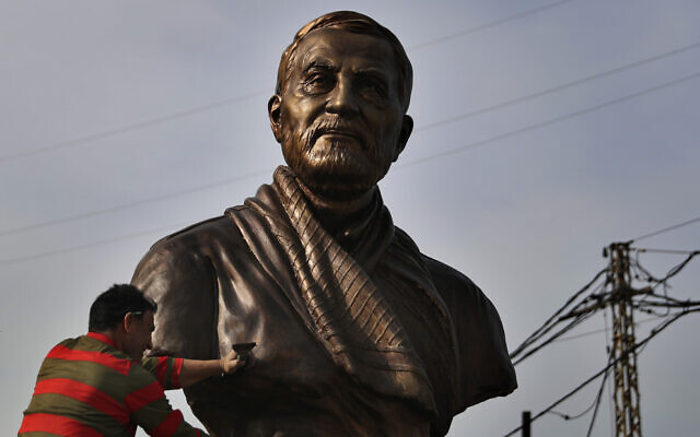 A worker cleans a statue of Iranian General Qassem Soleimani, installed to commemorate the anniversary of his killing, in a US drone strike in Baghdad, in Ghobeiry, a southern suburb of Beirut, Lebanon, January 6, 2021. (AP Photo/Bilal Hussein)