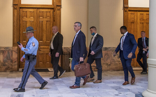 Led by a Georgia State Trooper, Georgia Secretary of State Brad Raffensperger, center, exits the Georgia State Capitol building after hearing reports of threats, January 6, 2021, in Atlanta. (Alyssa Pointer/Atlanta Journal-Constitution via AP)
