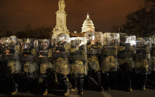 District of Columbia National Guard stand outside the Capitol, Wednesday night, Jan. 6, 2021, after a day of rioting protesters. (AP Photo/John Minchillo)