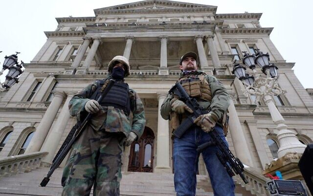 In this Jan. 6, 2021 file photo, armed men stand on the steps at the State Capitol after a rally in support of President Donald Trump in Lansing, Michigan (AP Photo/Paul Sancya, File)