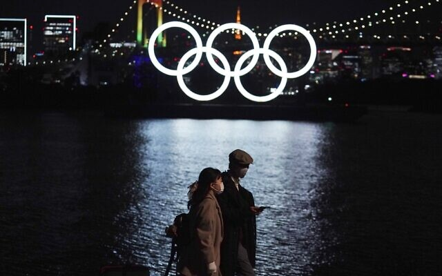 In this December 1, 2020 file photo, a man and a woman walk past near the Olympic rings floating in the water in the Odaiba section in Tokyo. (AP Photo/Eugene Hoshiko, File)