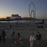 Tourists and residents enjoy the sunset at the Jumeirah Beach Residence, in Dubai, United Arab Emirates, January 12, 2021. (AP Photo/Kamran Jebreili)