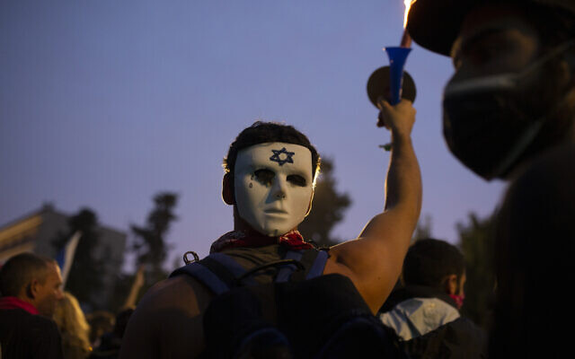 An anti-government protester wears a mask on the back of his head outside of the official residence of Prime Minister Benjamin Netanyahu on the day his corruption trial was originally scheduled before it was postponed, in Jerusalem, January 13, 2021. (Maya Alleruzzo/AP)