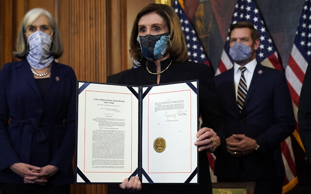 US House of Representatives Speaker Nancy Pelosi displays the signed article of impeachment against US President Donald Trump in an engrossment ceremony before transmission to the Senate for trial on Capitol Hill, in Washington, January 13, 2021. (AP Photo/Alex Brandon)