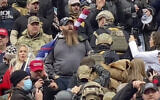 In this Jan. 6, 2021 image from video provided by Robyn Stevens Brody, a line of men wearing helmets and olive drab body armor walk up the marble stairs outside the US Capitol in Washington in an orderly single-file line, each man holding the jacket collar of the man ahead. The formation, known as 'Ranger File,' is standard operating procedure for a combat team 'stacking up' to breach a building. (Robyn Stevens Brody via AP)