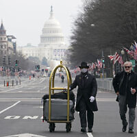 Danish Rozario, left, of Silver Spring, Maryland, wheels the baggage down Pennsylvania Avenue for a guest at the Trump Hotel in Washington, January 15, 2021, ahead of the inauguration of President-elect Joe Biden and Vice President-elect Kamala Harris. (AP Photo/Susan Walsh)