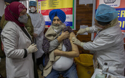 A hospital staff member receives a COVID-19 vaccine at a government Hospital in Srinagar, Indian controlled Kashmir, January 16, 2021. (AP Photo/ Dar Yasin)