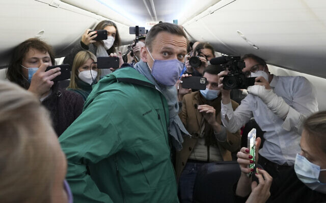 Alexei Navalny is surrounded by journalists inside the plane prior to his flight to Moscow in the Airport Berlin Brandenburg (BER) in Schoenefeld, near Berlin, Germany, January 17, 2021. (AP Photo/Mstyslav Chernov)