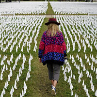 Artist Suzanne Brennan Firstenberg walks among thousands of white flags planted in remembrance of Americans who have died of COVID-19, near Robert F. Kennedy Memorial Stadium in Washington, October 27, 2020. (AP Photo/Patrick Semansky, File)