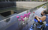 A mourner prays at the National September 11 Memorial and Museum in New York, September 11, 2020. (John Minchillo/AP)