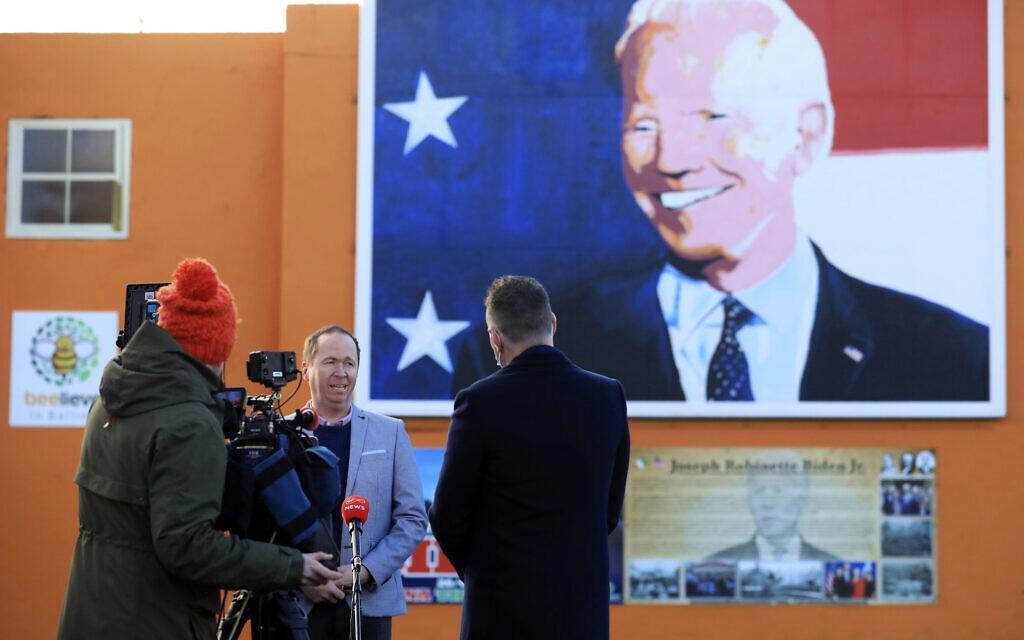 Joe Biden's cousin Joe Blewitt speaks to the media underneath his mural painted on a wall in Ballina, Ireland, January 20, 2021. (AP Photo/Peter Morrison)