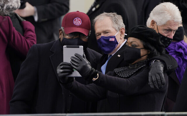 House Majority Whip James Clyburn of South Carolina, left, and former US President George Bush, take a selfie before the 59th Presidential Inauguration at the US Capitol in Washington, January 20, 2021. (Patrick Semansky/AP)
