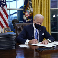 US President Joe Biden signs his first executive order in the Oval Office of the White House on January 20, 2021, in Washington. (AP Photo/Evan Vucci)