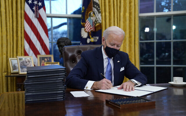 US President Joe Biden signs his first executive order in the Oval Office of the White House on Wednesday, Jan. 20, 2021, in Washington. (AP Photo/Evan Vucci)