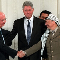 Then US President Bill Clinton, center, looks on as Israeli Prime Minister Yitzhak Rabin, left, and PLO leader Yasser Arafat shake hands in the East Room of the White House after signing the Middle East accord in Washington on September 28, 1995. (AP Photo/Doug Mills, File)