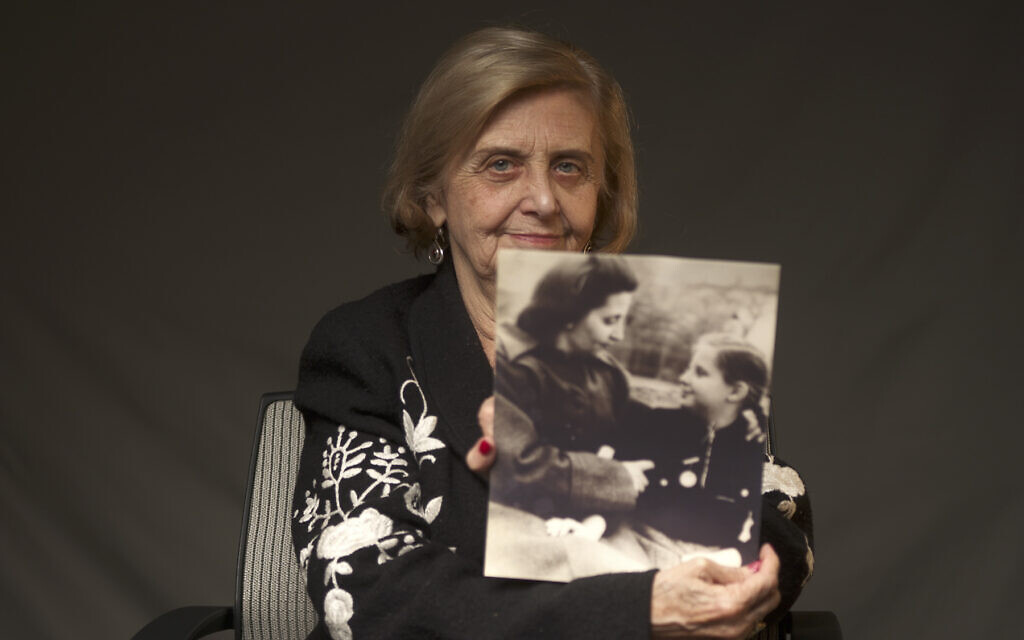 Illustrative: Tova Friedman, an 82-year-old Polish-born Holocaust survivor, holds a photograph of herself as a child with her mother, who also survived the Nazi death camp Auschwitz, in New York, December 13, 2019. (World Jewish Congress via AP)