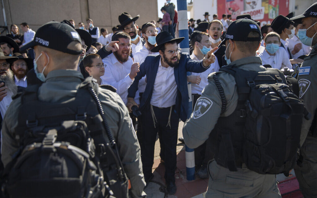 Ultra-Orthodox Jews argue with Israeli border police officers during a protest over the coronavirus lockdown restrictions, in Ashdod, January 24, 2021. (AP/Oded Balilty)