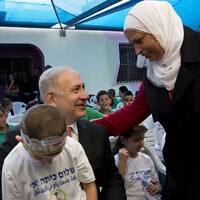 Illustrative: Prime Minister Benjamin Netanyahu poses for a photograph with pupils on the first day of school in the Israeli Arab town of Tamra, Thursday, September 1, 2016. (AP/Sebastian Scheiner)