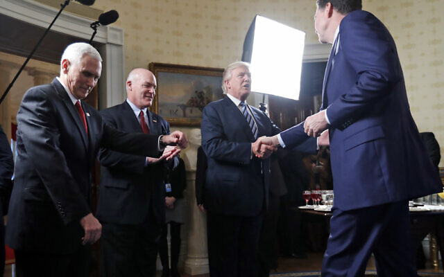 In this this Jan. 22, 2017, file photo, Vice President Mike Pence, left, and Secret Service Director Joseph Clancy stand as President Donald Trump shakes hands with then-FBI Director James Comey during a reception for inaugural law enforcement officers and first responders in the Blue Room of the White House in Washington. (AP Photo/Alex Brandon)