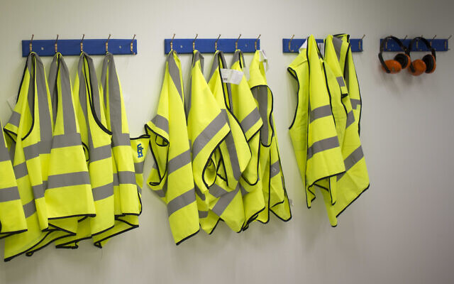 Illustrative: Safety jackets hang at a factory in southern Israel on March 13, 2018. (AP/Ariel Schalit)
