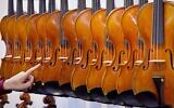 Illustrative -- Violins hang next to each other at the Music Fair in Frankfurt, Germany, April 11, 2018. (AP Photo/Michael Probst)