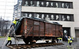 Illustrative: Portraits of Holocaust survivors are displayed at the Museum of Jewish Heritage as a vintage German train car, like those used to transport people to Auschwitz and other death camps, is uncovered on tracks outside the museum, in New York, Sunday, March 31, 2019.  (AP Photo/Richard Drew)