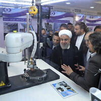 """In this April 9, 2018 photo, Iranian President Hassan Rouhani listens to explanations on new nuclear achievements at a ceremony to mark """"National Nuclear Day,"""" in Tehran, Iran. (Iranian Presidency Office via AP)"""