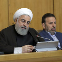 Iranian President Hassan Rouhani speaks during a cabinet meeting, as his chief of staff Mahmoud Vaezi sits at right, in Tehran, Iran, July 10, 2019. (Iranian Presidency Office via AP)