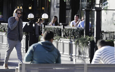 Illustrative -- People sit in an outdoor restaurant area in Christchurch, New Zealand, June 8, 2020 (AP Photo/Mark Baker)