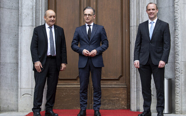 German Foreign Minister Heiko Maas, center, welcomes the Foreign Minister of Great Britain, Dominic Raab, right, and the Foreign Minister of France, Jean-Yves Le Drian, left, for a meeting in Berlin, Germany, June 19, 2020. (Bernd von Jutrczenka/DPA via AP, Pool)